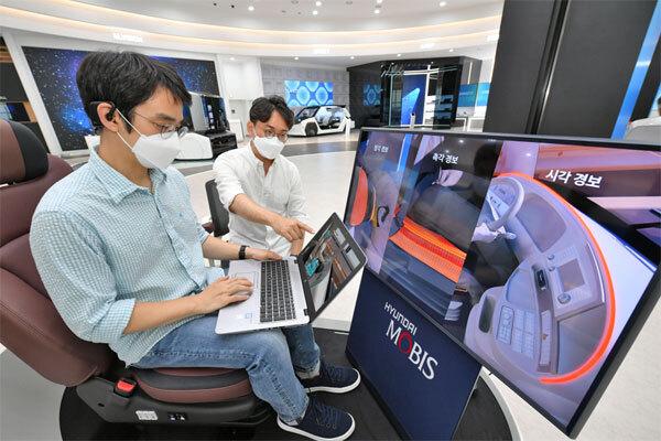 현대모비스의 뇌파 측정 기반 운전자 모니터링 시스템 `엠브레인`을 개발한 연구원들이 관련 기술을 시험하고 있다.  [사진 제공 = 현대모비스]