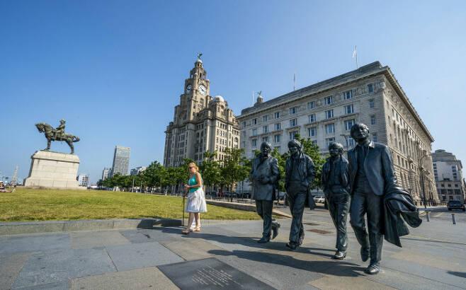 영국 리버풀 부둣가의 로열 리버 빌딩 앞에 세워진 록밴드 비틀스의 동상 앞으로 21일(현지시간) 한 시민이 지나가고 있다. 리버풀 | AP연합뉴스