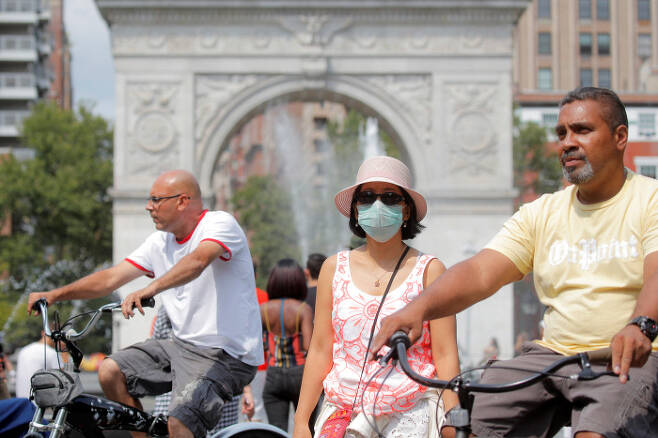 마스크를 쓴  시민과 그렇지 않은 미국 시민들이 22일(현지시간) 뉴욕의 워싱턴 스퀘어 공원을 지나가고 있다. 뉴욕|로이터연합뉴스