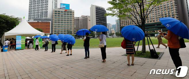 전국 대부분 지역에 폭염특보가 발효된 28일 중구 서울광장에 마련된 코로나19 임시선별검사소에서 갑자기 소나기가 내리자 시민들이 우산을 쓴채 줄 서 있다. 2021.7.28/뉴스1 © News1 안은나 기자