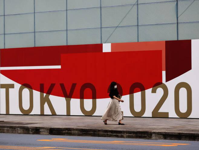 한 여성이 마스크를 쓴 채 29일 2020 도쿄올림픽 로고가 새겨진 벽화 앞을 지나고 있다. (사진=AFPBBNews)