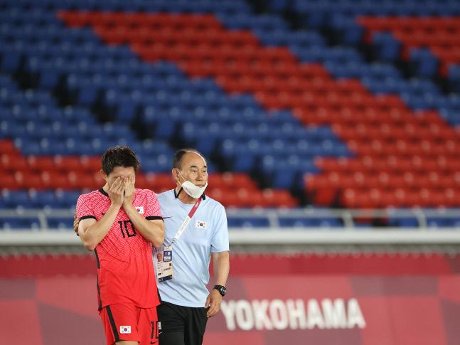 김학범(오른쪽) 올림픽축구대표팀 감독이 지난달 31일 요코하마 국제경기장에서 열린 도쿄올림픽 남자축구 8강전 멕시코전에서 3-6 완패한 뒤 눈물을 흘리는 이동경을 위로하고 있다. 요코하마   연합뉴스