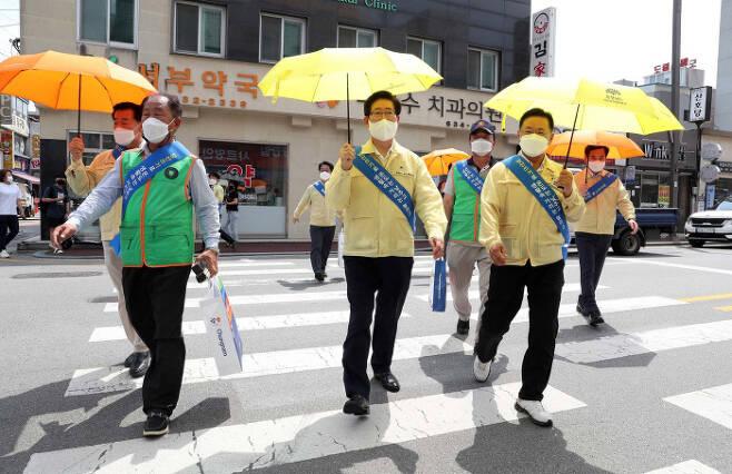 양승조 충남도지사(앞줄 가운데)가 지난달 30일 충남 홍성읍내에서 양산쓰기 캠페인을 벌이고 있다. 충청남도 제공