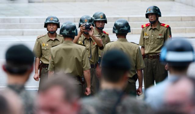 정전협정 64주년인 2017년 7월 27일 판문점에서 북한 병사들이 정전기념 행사에 참여해 기념사진을 찍는 참전국 대표단을 배경으로 기념사진을 찍고 있다. 한국일보 자료사진