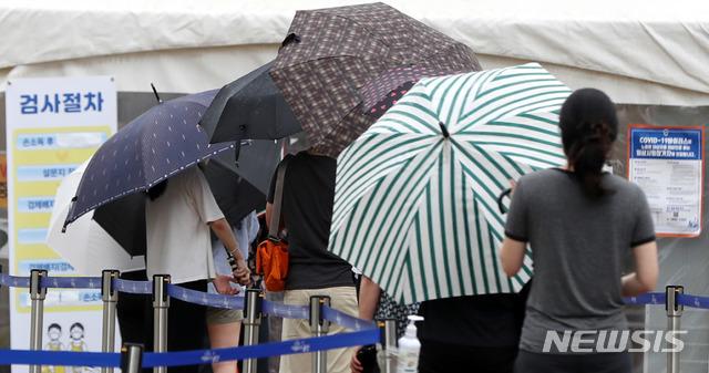 [서울=뉴시스] 추상철 기자 = 비가 내린 2일 오전 서울 용산역 임시선별진료소에서 우산을 쓴 시민들이 코로나19 검사를 받기 위해 줄 서 있다. 2021.08.02. scchoo@newsis.com