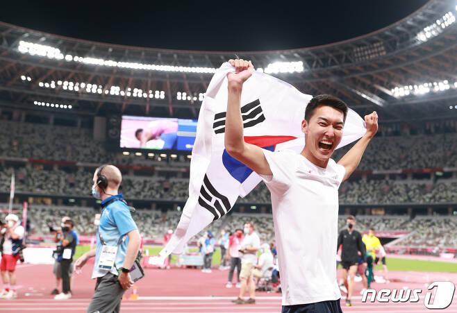 2.35m를 넘으며 한국 육상 높이뛰기 신기록을 세운 우상혁 선수가 올림픽스타디움에서 태극기를 흔들고 있다. 2021.8.1/뉴스1 © News1 올림픽사진취재단
