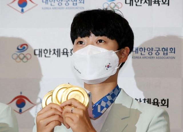 양궁 3관왕 안산이 1일 오후 영종도 인천국제공항을 통해 귀국한 뒤 금메달을 들어보이고 있다. 연합뉴스