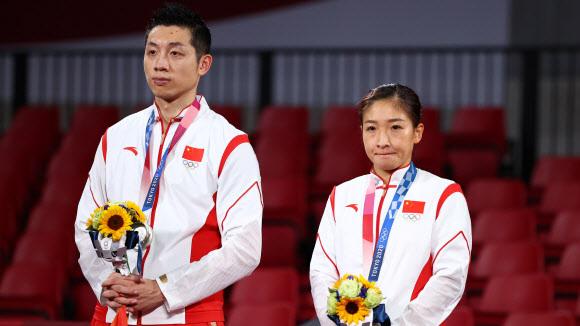 지난달 26일 도쿄올림픽 탁구 혼합복식 결승에서 일본에 져 은메달을 딴 중국 대표팀 쉬신(왼쪽)과 류스원이 침울한 표정으로 시상대에 서 있다. 이들은 금메달을 못 딴 데 대해 국민들에게 눈물로 사죄를 해야 했다.도쿄 로이터 연합뉴스