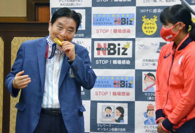 가와무라 다카시 일본 나고야 시장(왼쪽)이 지난 4일 나고야시청을 방문한 도쿄올림픽 소프트볼 금메달리스트 고토 미우의 메달을 양해도 구하지 않은 채 깨물고 있다. 나고야/교도연합뉴스