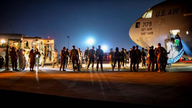 아프간 피난민들이 2021년 8월 24일 쿠웨이트 알리 알 살렘 공군기지에 도착한 후 미국 C-17 글로벌 마스터를 떠나고 있다. 쿠에이트 | 로이터연합뉴스