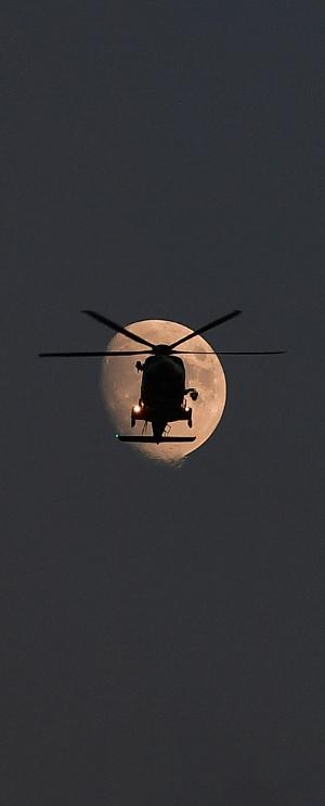 지난 19일 인천 영종도 하늘에서 밝게 뜬 달 앞으로 해경 구조헬기가 순찰 비행을 하고 있다.
