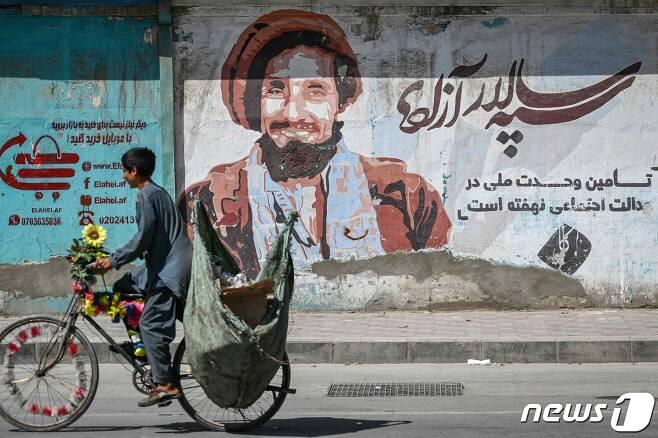 8일 (현지시간) 아프가니스탄 카불에서 '국부' 아흐마드 샤 마수드의 초상화 앞을 청소년이 자전거를 타고 가고 있다. © AFP=뉴스1 © News1 우동명 기자