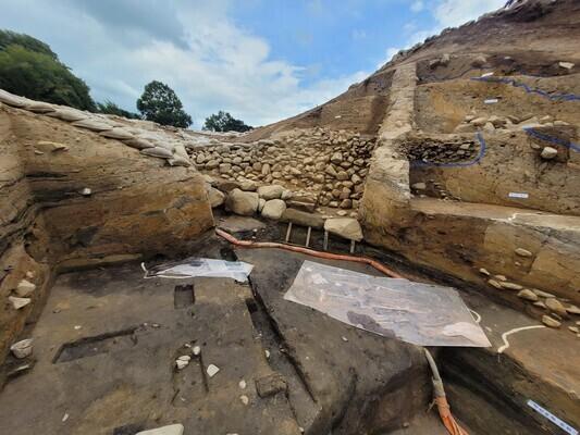 지난 7일 월성 서성벽 서문 추정터의 발굴 현장을 찍은 사진. 부엽 공법 등을 써서 태운 볏짚층 때문에 거멓게 변색된 기저층 위에 2017년과 올해 발굴된 남녀 인골과 여성 인골의 프린트 종이들이 각각 놓여 있다. 출토 지점 위쪽에는 길쭉한 큰 돌을 잇따라 놓고 그 위에 돌들을 쌓아올린 성벽의 중심골조 부분이 보인다. 중심골조 옆으로는 흙을 덧쌓아 성벽의 너비를 넓힌 성토 흔적이 드러나 있다.