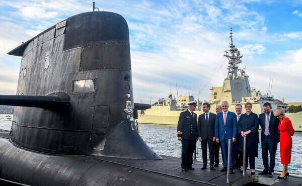 에마뉘엘 마크롱 프랑스 대통령(왼쪽 두 번째)과 맬컴 턴불 오스트레일리아 총리(가운데)가 2018년 5월 2일 시드니 가든 아일랜드에서 오스트레일리아 해군의 콜린스급 잠수함 'HMAS 웨일러'의 선체 위에 서 있다. 오스트레일리아는 15일(현지시각) 미국·영국과 3국간 안보협력체인 '오커스'의 발족과 함께 미국의 기술 지원으로 핵추진잠수함 개발에 나서면서, 프랑스와 추진해온 660억 달러(약 77조원) 규모의 재래식 잠수함 건조 계획을 철회할 것으로 예상된다. AFP 연합뉴스 자료사진