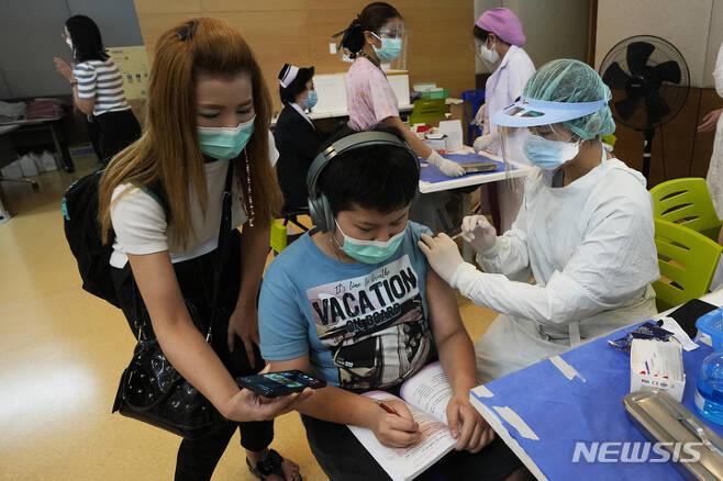 [방콕(태국)=AP/뉴시스]태국 방콕의 한 병원에서 21일 코로나19 백신을 접종받은 한 아이의 어머니가 옆에서 아들에게 휴대전화 화면을 보여주고 있다. 태국 보건 당국이 21일 기저질환이 있는 12∼18세의 아이들에게 화이자의 코로나19 백신을 접종하기로 결정했다. 2021.9.21