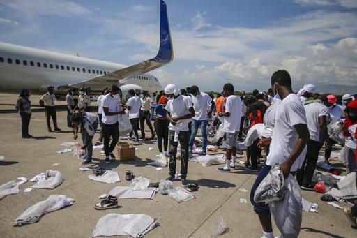지난 21일(현지시간) 아이티포르토프랭스투생 루베르튀르국제공항에서 미국에서 수송기를 타고 추방된아이티 난민들이 소지품을 챙기고 있다.포르토프랭스=AP연합뉴스