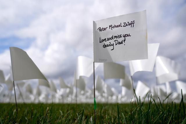 21일 미국 워싱턴 내셔널 몰에 설치된 하얀 깃발에 코로나19 희생자를 추모하는 메시지가 적혀 있다. 워싱턴=AP 연합뉴스