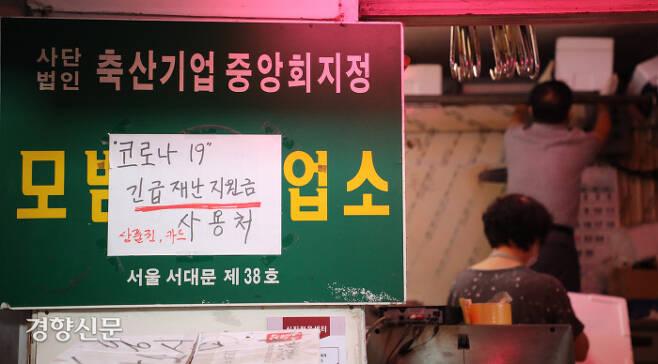 제5차 긴급재난지원금 신청이 시작된 9월 6일 서울 서대문구 인왕시장 내 정육점 사장 부부가 '재난지원금 사용처'가 적힌 종이를 붙이고 내부를 정리하고 있다. / 박민규 선임기자