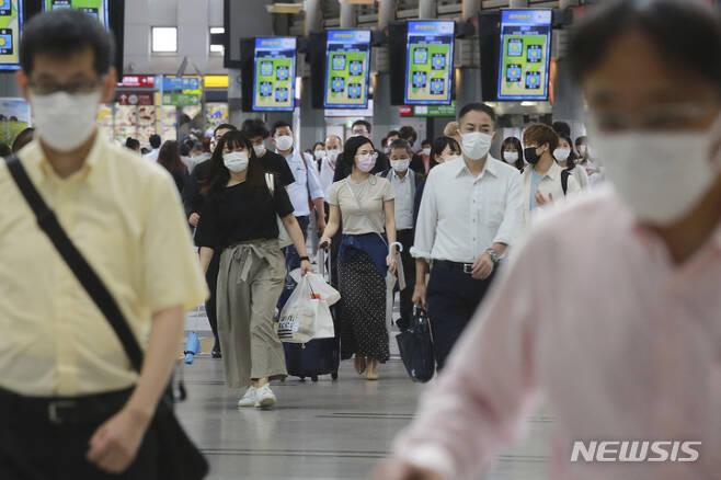 [도쿄(일본)=AP/뉴시스]지난 6일 일본 도쿄의 한 지하철 역에서 시민들이 코로나19 감염 예방을 위해 마스크를 쓴 채 걷고 있다. 2021.09.08