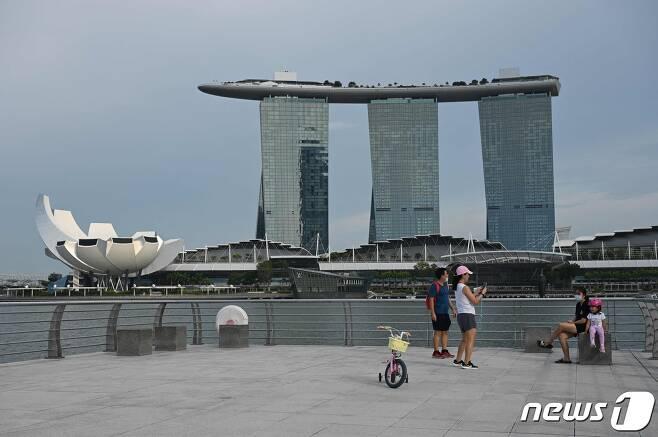 13일(현지시간) 싱가포르 마리나베이샌스 호텔(오른쪽)과 아트사이언스 박물관(왼쪽)이 보이는 공원에서 사람들이 사진 촬영을 하고 있다. 2021.10.13 © AFP=뉴스1