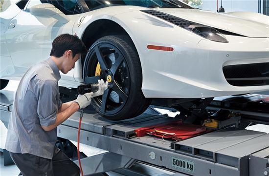 차량 정비소 직원이 타이어 상태를 점검하고 있다.