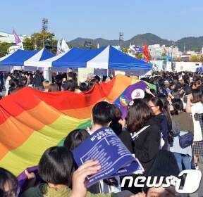 무지개기 흔들며 자축하는 퀴어문화축제 참가자들